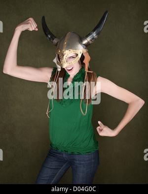 Junge Frau in der Wikinger-Helm lässt ihre Muskeln spielen - Stockfoto