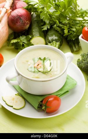 Foto von vegetarische Gemüsesuppe am grünen Tisch aus Holz mit verschiedenen Gemüsen arround - Stockfoto