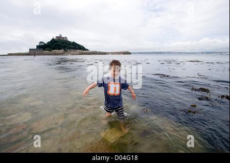 7 Jahre alten Sohn zu Fuß durch tief Gezeiten-Wasser auf St Michaels Mount Damm, Marazion, Cornwall. - Stockfoto