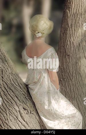 eine Frau in einem geblümten Kleid sitzt auf einem Stamm - Stockfoto