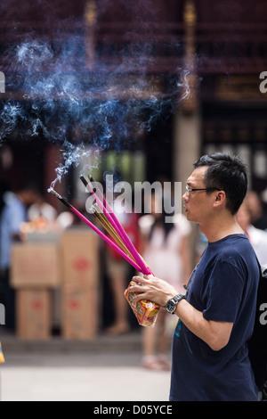 Ein Mann betet Chenghuang Miao oder City God Temple in Yu Yuan Gardens Basar Shanghai, China - Stockfoto