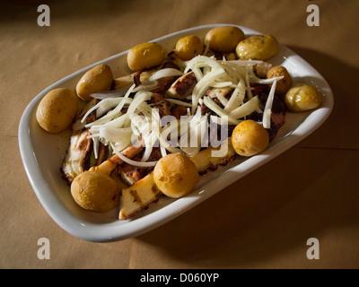 Typisch portugiesisches Gericht Polvo À Lagareiro - Oktopus gekocht mit Kartoffeln und beträufelt mit Olivenöl, - Stockfoto