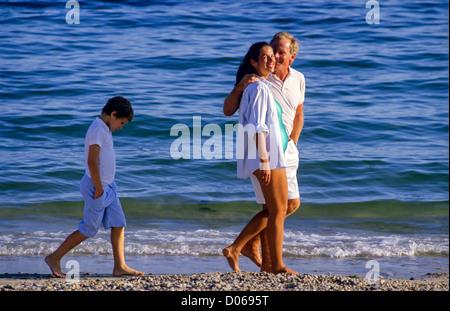 Unglückliche Junge hinter Paar mit schwangeren Frau am Strand - Stockfoto