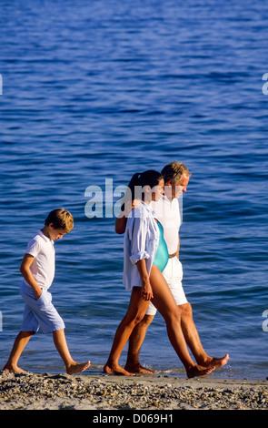 Sulky junge zu Fuß hinter paar mit schwangere Frau am Strand - Stockfoto