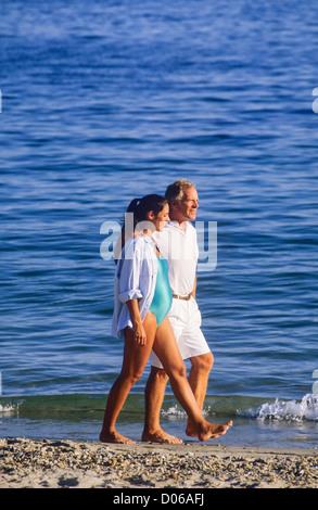 Paar mit schwangere Frau spazieren am Strand - Stockfoto