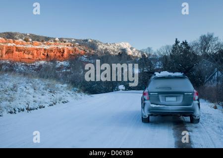 Passagier Auto und Schnee bedeckten Straße in Colorado Backcountry mit roten Sandsteinfelsen - Stockfoto