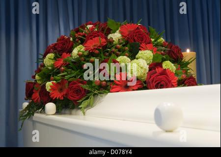 Ein weißer Sarg in einer Leichenhalle mit einem Blumen-arrangement ...
