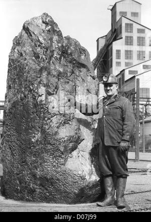 Mann steht neben großen Stück Anthrazit - Stockfoto