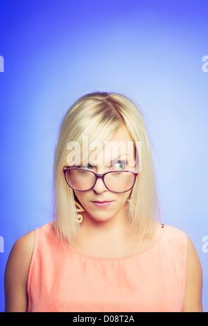 Porträt einer jungen skeptisch Frau isoliert auf blauem Hintergrund - Stockfoto