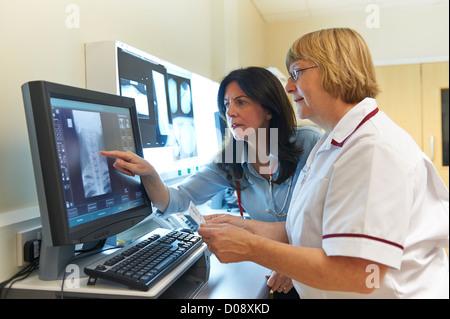 Arzt und MTRA zusammen mit Blick auf eine X-Ray Bild auf dem Bildschirm zeigt einen Abschnitt der menschlichen Wirbelsäule - Stockfoto