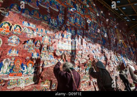 Pilger-Gottesdienst in Grotte geschnitzt aus Stein, Chapori Schrein am Jabore Berg im zentralen Lhasa, Tibet, China - Stockfoto