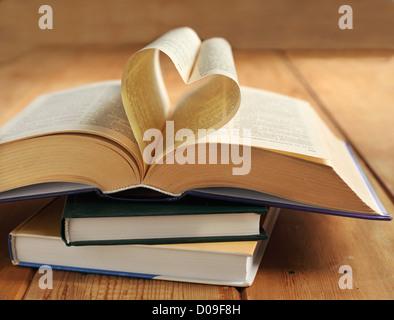 Aufgeschlagenes Buch. Seiten des Buches in Form eines Herzens gefaltet - Stockfoto