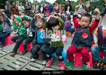 Schülerinnen und Schüler handeln Zeichen während Märchenstunde Wenhua Park, Chengdu, Provinz Sichuan, China - Stockfoto