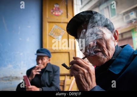 Mann raucht Pfeife beim Karten spielen mit Freunden am Markttag in Dorf am Stadtrand von Chengdu, Provinz Sichuan, - Stockfoto