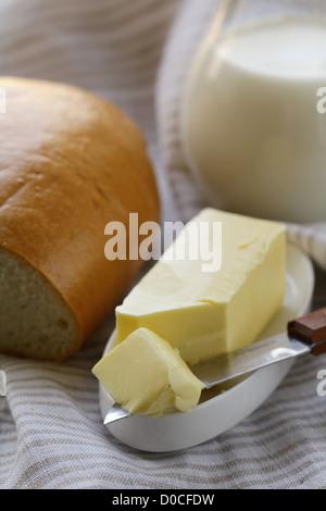 Butter, Laib Weißbrot und Milch auf Holzplatte - Stockfoto