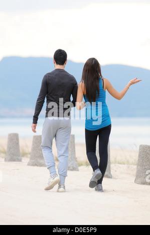 Junges Paar zu Fuß am Strand - Stockfoto