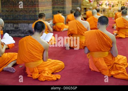 Mönche beten in Phra Ubosot Hall, Tempel Wat Pho, Bangkok, Thailand - Stockfoto