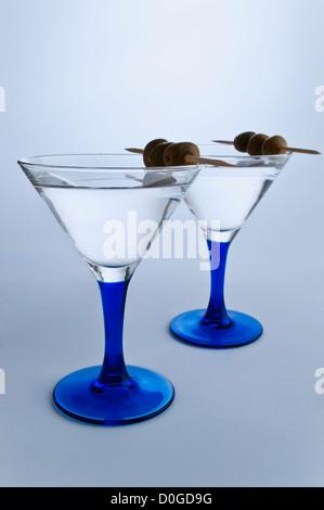 Zwei stilvolle Martinigläser auf graue weißem Hintergrund. Zwei Martini mit Oliven - Stockfoto