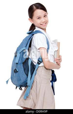 Glücklich Schulmädchen mit Büchern und Schultasche auf dem Rücken - Stockfoto