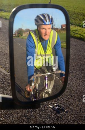 Radfahrer tragen Warnschutz Kleidung Refelected im Fahrzeug Außenspiegel auf Straße in der Nähe von Leeds United - Stockfoto