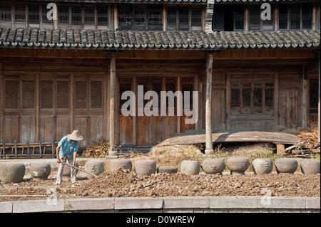 Ein Landwirt arbeiten vor einem alten chinesischen Holzhaus - Stockfoto