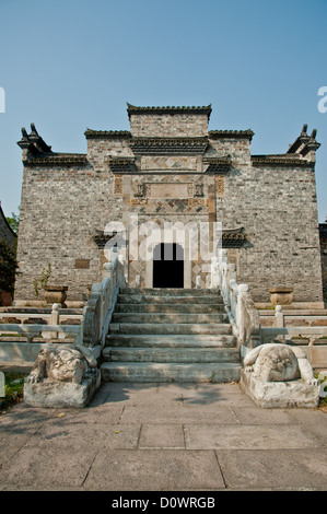 Die Vorderseite eines alten chinesischen Ziegel-Haus mit geschnitzten Balken und Traufe - Stockfoto