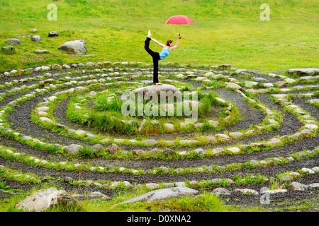 Frau mit Regenschirm in Yoga-Pose im Zentrum von Stein Labyrinth - Stockfoto