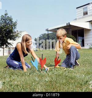 1970ER JAHRE JUNGE MÄDCHEN SPIELEN LAWN DARTS SPIEL IM HINTERHOF - Stockfoto