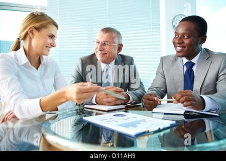 Porträt von hübschen Sekretärin zeigt auf Papier etwas zu ihrem Chef und Kollegen zu erklären - Stockfoto