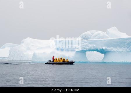 Eine Gruppe von Touristen In gelben Jacken In ein Zodiac Reisen durch Eisberge; Antarktis - Stockfoto