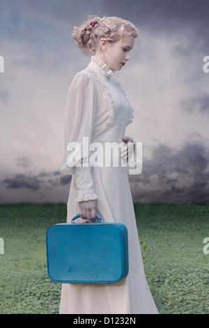 eine junge Frau in einem viktorianischen Kleid mit einem blauen Koffer Stockfoto