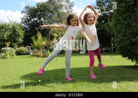 Schwestern tragen die gleichen Ballerina T-Shirt und tanzen im Garten Surrey England - Stockfoto