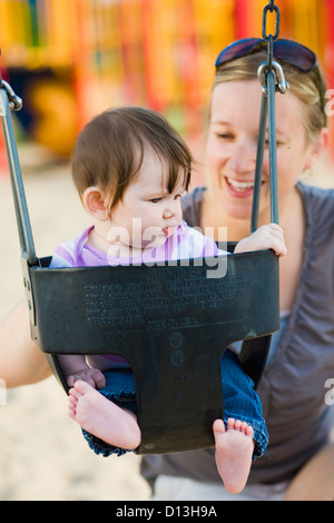 Frau In ihren späten 20. In einem Park mit ihren 6 Monate alten Tochter In einem Schwung; Ontario Kanada - Stockfoto