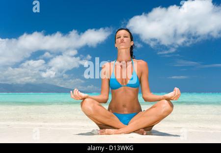 Frau praktizieren Yoga am tropischen Strand, Lotus-Position. - Stockfoto