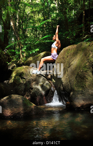 Hawaii, Oahu, junges Weibchen Yoga In einem üppigen Wald mit Wasserfall unter ihr zu tun. - Stockfoto