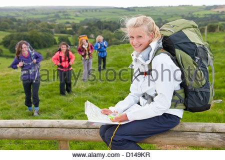 Porträt von lächelndes Mädchen mit Rucksack und Karte auf Zaun im Bereich - Stockfoto