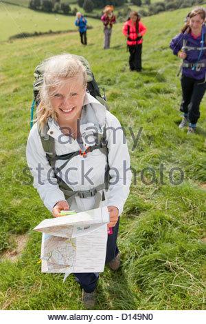 Porträt von lächelndes Mädchen mit Rucksack und Karte im Feld - Stockfoto