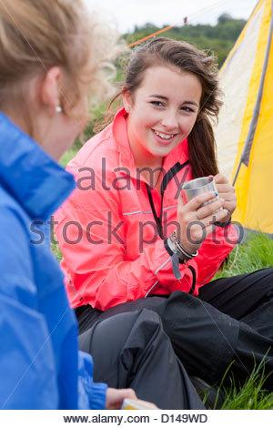Nahaufnahme des Lächelns Mädchen trinken Tee neben Zelt - Stockfoto