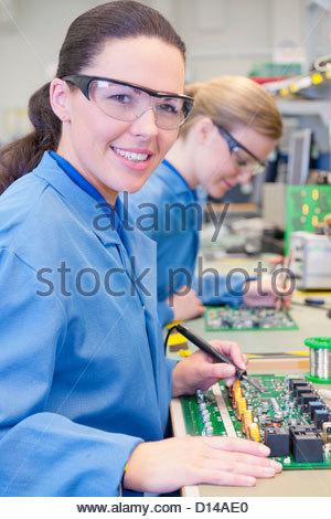 Porträt des Lächelns Techniker lötenden Platine im Werksgelände - Stockfoto