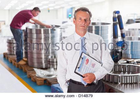 Porträt von Ernst Manager mit Klemmbrett in Stahl mit Produktionsstätte - Stockfoto