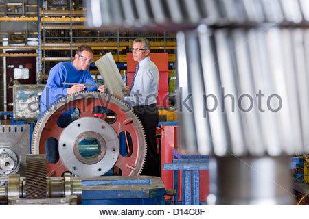 Ingenieur und Arbeitskraft Inspektion Zahnräder in Fabrik - Stockfoto