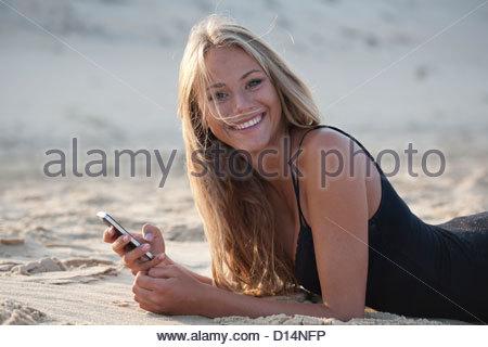 Frau mit Handy am Strand - Stockfoto