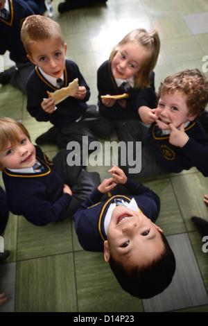 Ein Schuljunge Essen Toast nach Morgen Versammlung in Our Lady & St. Werburgh's katholische Grundschule in Newcastle - Stockfoto