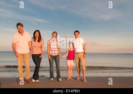 Familie lächelnd zusammen am Strand - Stockfoto