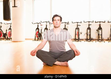 Menschen, die meditieren auf Matte zu Fitness-Studio - Stockfoto