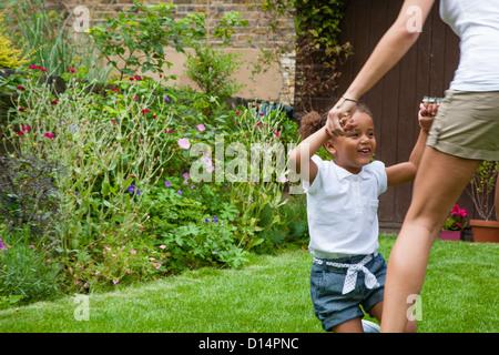 Mutter und Tochter tanzen im Garten - Stockfoto