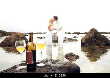 Hawaii, Oahu, Hochzeit paar Küssen In der Tidepool mit Flasche Wein und zwei Gläser links auf einem Felsen im Vordergrund. - Stockfoto