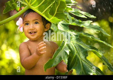 Hawaii, Oahu, Baby Mädchen mit Wasser spielen. - Stockfoto