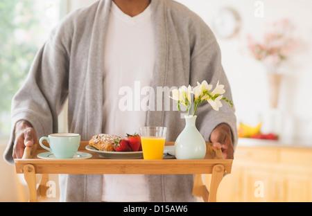 USA, New Jersey, Jersey City, junger Mann, hält Frühstückstablett - Stockfoto