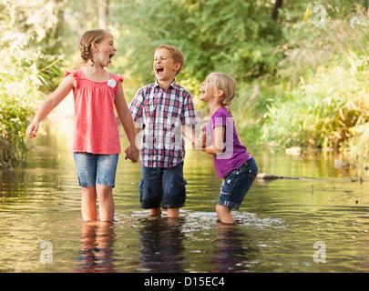 USA, Utah, Lehi, drei Kinder (4-5, 6 und 7) spielen zusammen in kleinen Bach - Stockfoto